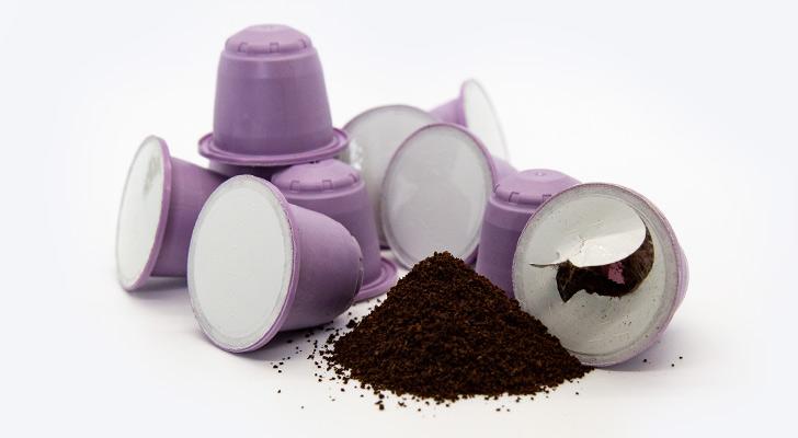 Defekte Kaffeekapsel mit Kaffee vor intakten